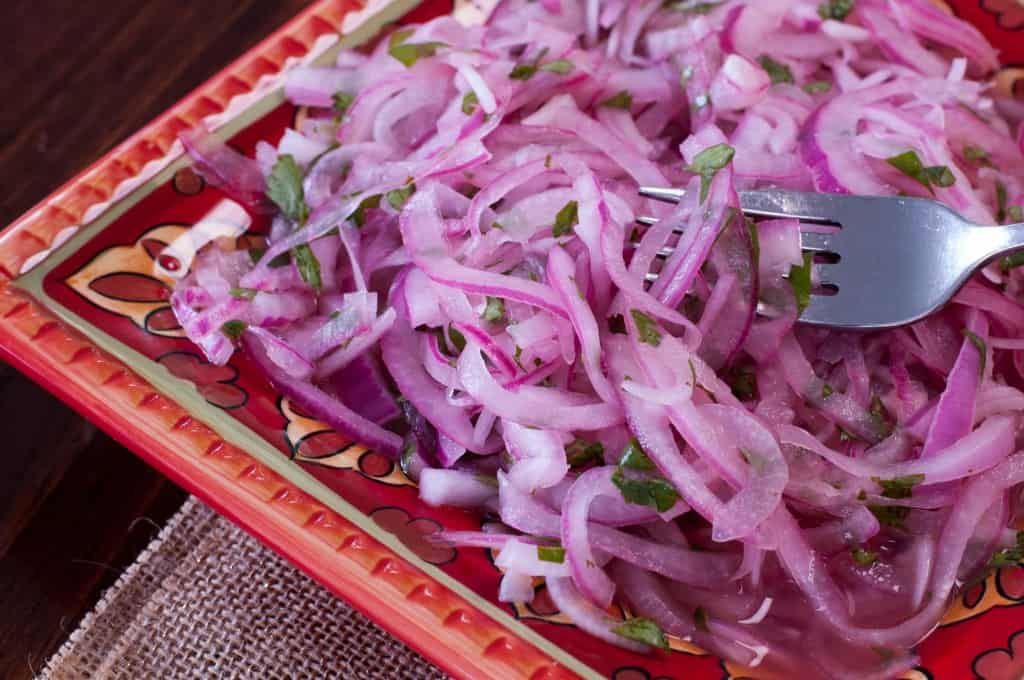 Colorful red pattered plate topped with pink marinated red onions, soaking in their juices with a silver fork