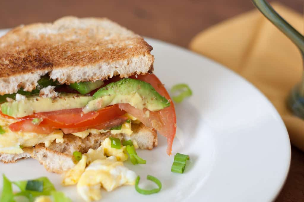 Breakfast sandwich with eggs, avocado, tomatoes, green onions