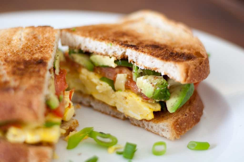 Grown Up Breakfast Sandwich with seasoned eggs, fresh tomatoes, buttery avocado, and green onions served on crusty bread