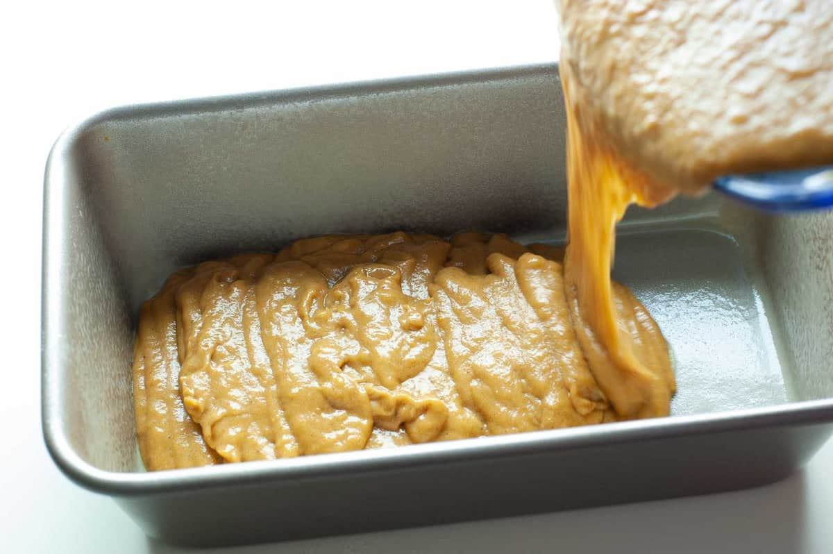 pumpkin banana bread batter being slowly poured into a silver bread pan