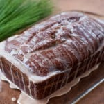 pumpkin banana bread loaf drizzled with cinnamon glaze on a clear platter with pine needles in the background