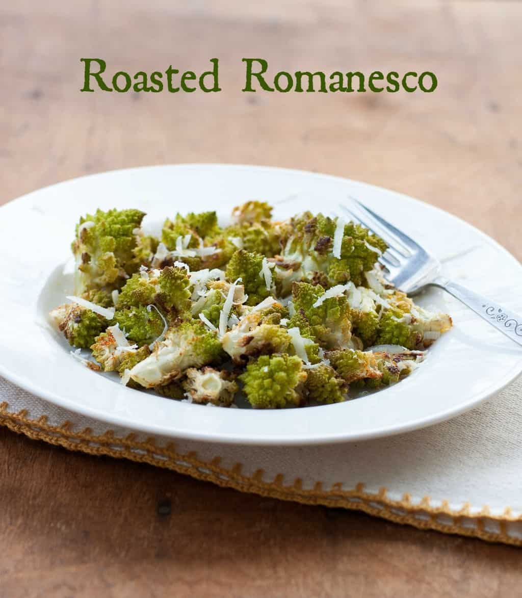 White bowl filled with roasted romanesco with shredded Pecorino Romano on top with a fork and napkin on a wooden tabletop with the test Roasted Romanesco at the top