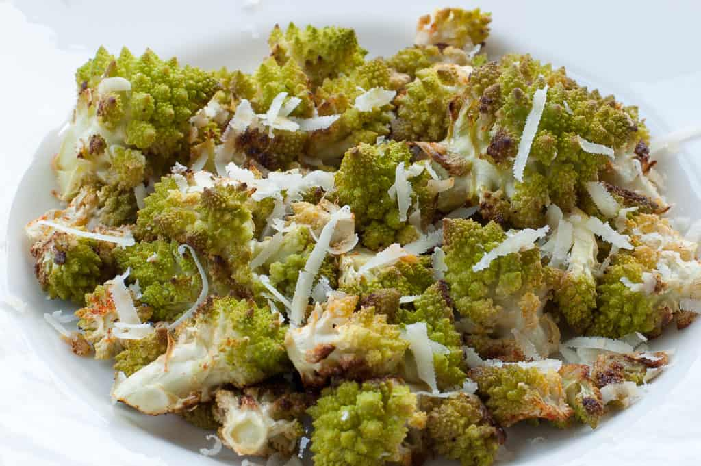 Closeup view of roasted romanesco pieces in a white bowl with shredded Pecorino Romano sprinkled on top