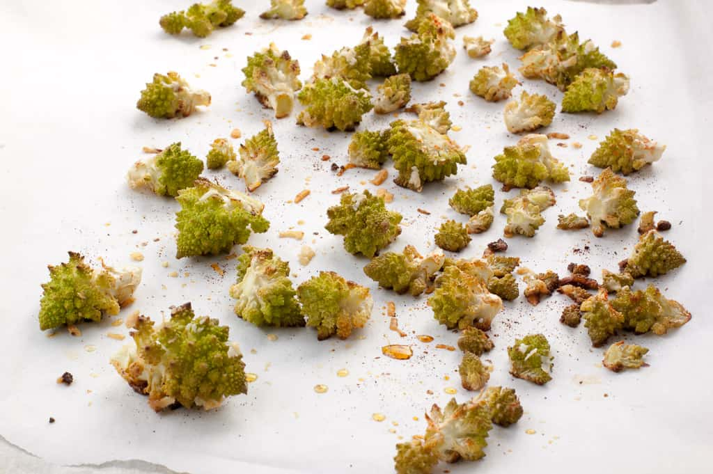 Roasted romanesco with browned bits scattered on a white parchment paper background