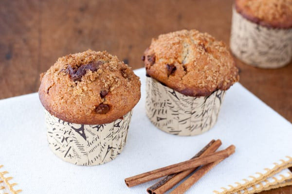 3 cinnamon muffins with chunks of cinnamon chips and crunchy cinnamon and sugar on top