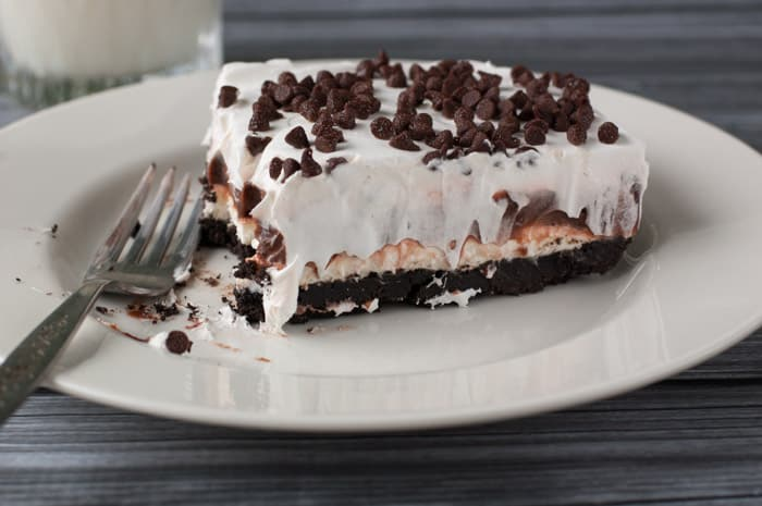 Slice of chocolate lasagna with a bite taken out on a white plate with whipped cream dripping down the sides