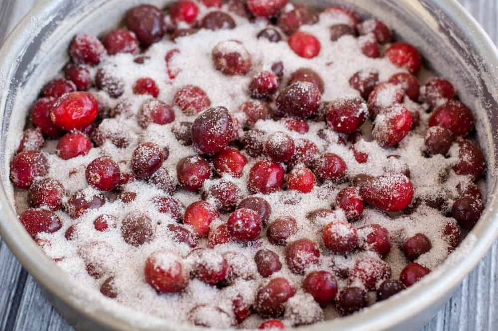 Silver cake pan filled to the rim with fresh cranberries and lots of sugar and spices