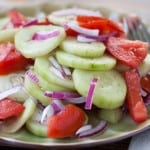 Piles of cucumber, tomatoes, and red onion dressed with a red wine vinaigrette on a green plate