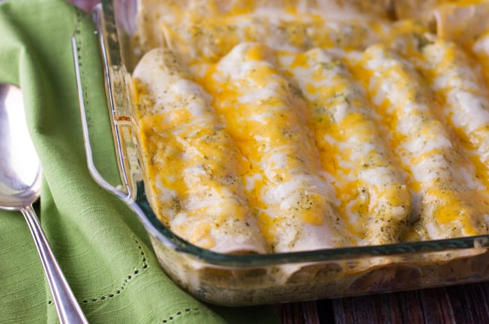 tortillas rolled up next to each other tightly in a casserole dish with melted cheese on top with a green napkin and large silver serving spoon