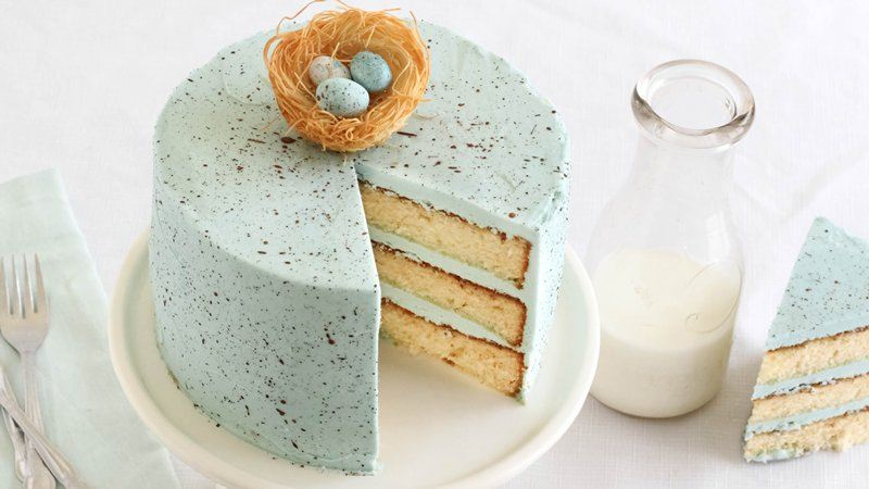 Slice taken out of white cake with thick light blue frosting with brown speckles next to a carafe of milk