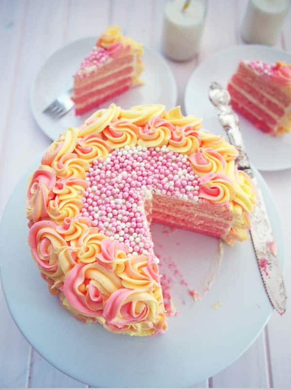 Pink ombre cake layers with yellow and pink frosting and large pink and white beaded candies on top