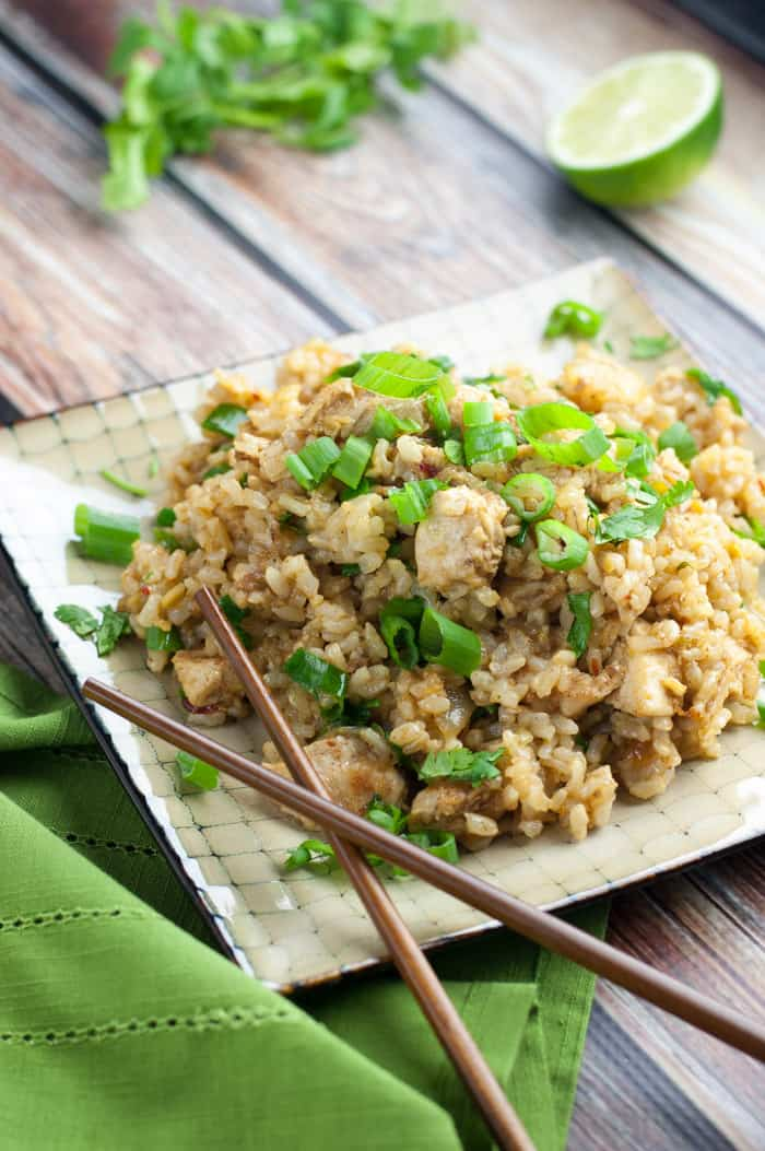 top view of spicy chicken fried rice topped with green onions on a square beige plate with brown wooden chopsticks