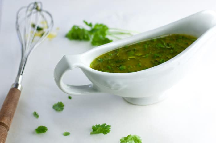 Side view of white gravy boat filled with honey lime cilantro sauce and silver whisk with wood handle next to it