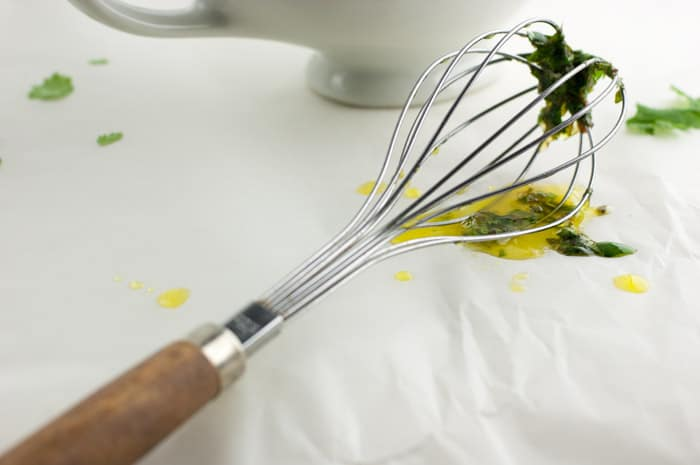 wooden and metal whisk with bits of honey lime cilantro sauce stuck to the end and drips of it all over parchment paper