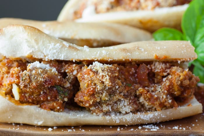 Closeup of meatball sub sandwich filled with moist meatballs covered in sauce and sprinkled with Pecorino Romano cheese