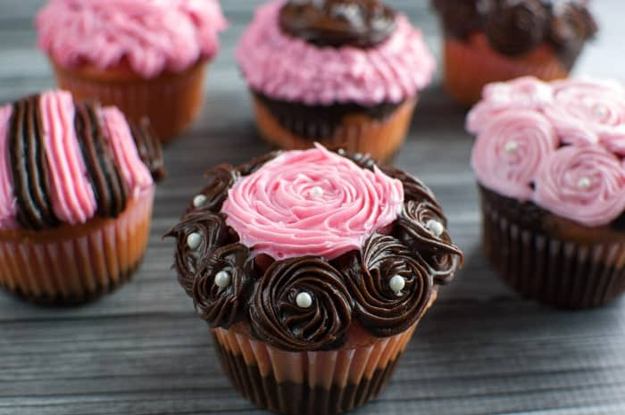 Closeup of pink and brown swirled frosting cupcake with white pearl candies with other cupcakes in the background