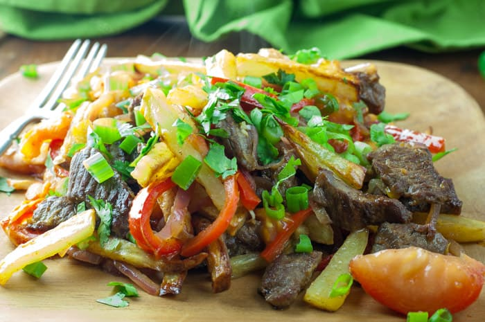 Lomo Saltado - a Peruvian beef stir-fry with bold flavors. Top with Peruvian Green Sauce or Salsa Criolla - one of my favorite dishes from El Pollo Inka