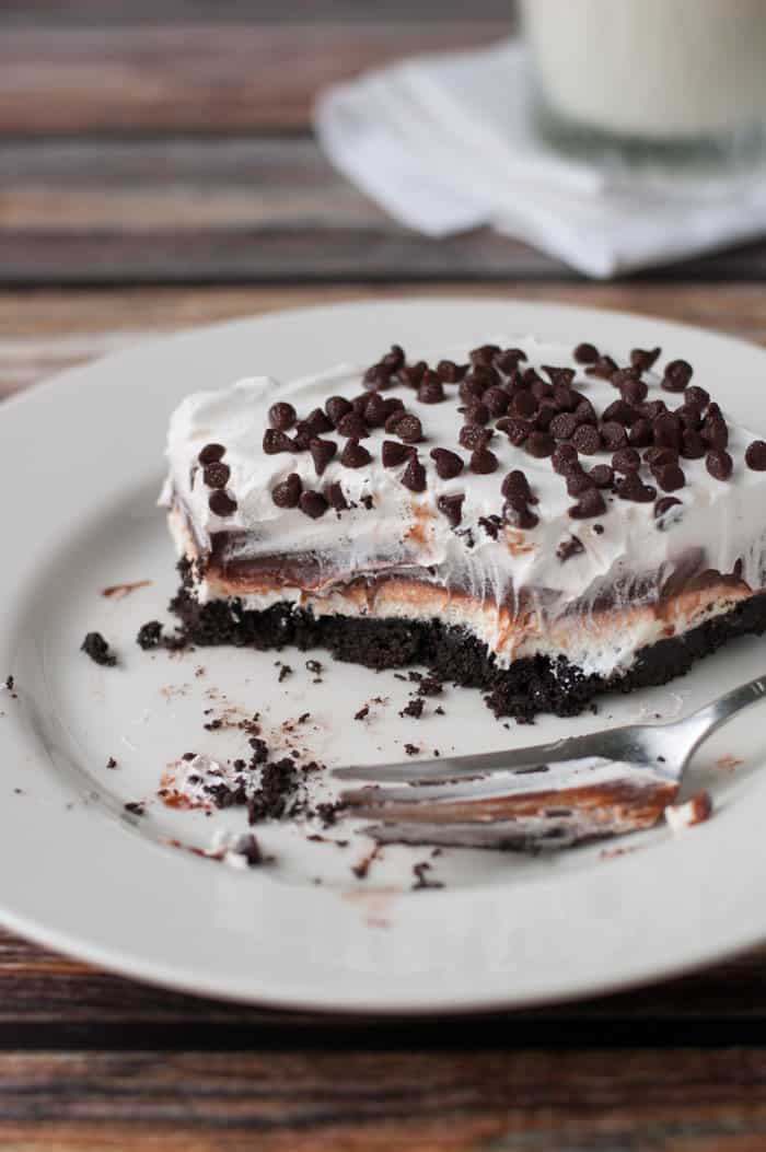 thick layers of cookie crust, cream cheese, chocolate pudding, whip cream and chocolate chips on top half eaten on a plate with a glass of milk
