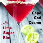 Side view of bright red cape cod cosmopolitan with no ice and a green lime sugared rim with 2 half used limes in the background