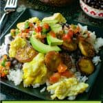 Rice, scrambled eggs, black beans, salsa, avocados, and plantains piled high on a black square plate with a bowl of salsa and sliced avocados in the background