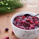 White bowl filled with cranberry sauce and a silver spoon with text that says Homemade Cranberry Sauce - Ready in 20 minutes