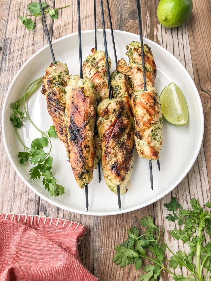 Five chicken skewers on a white plate with lime and cilantro