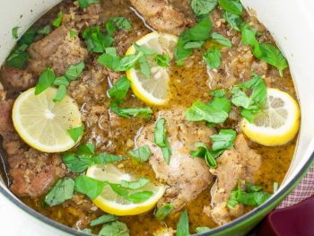 Seared chicken thighs and lemon slices with chopped basil in a green stock pot