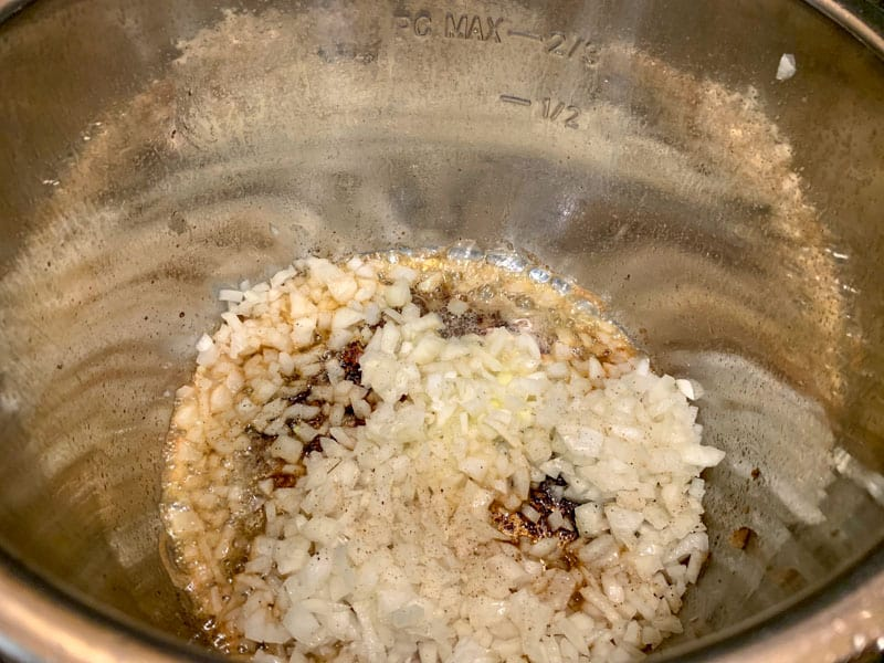 Chopped raw onions sauteing in an Instant Pot