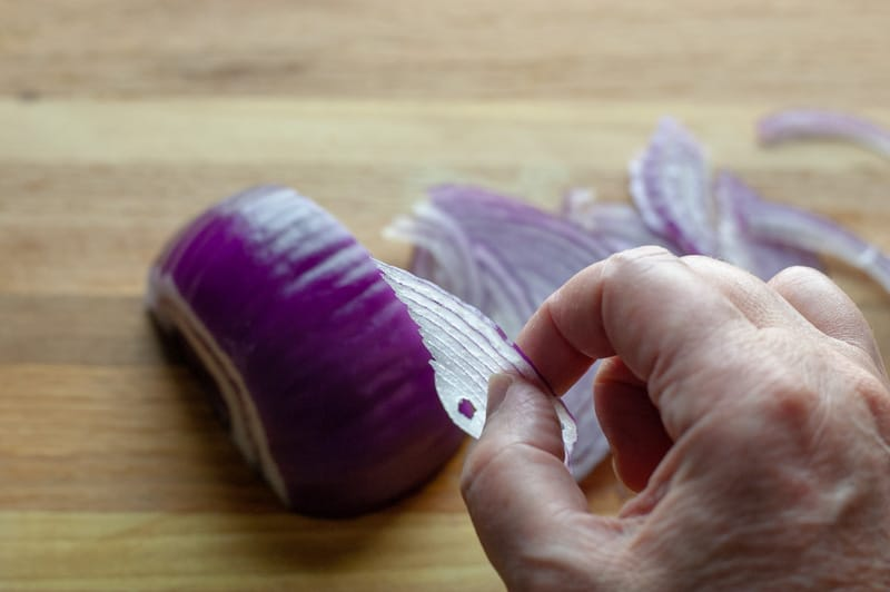 hand holding sliced red onions to show how thinly to slice them for salsa criolla