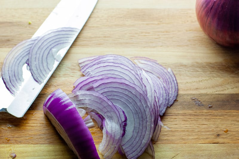 Thinly sliced red onions on a wooden cutting board