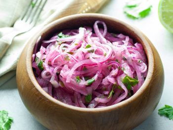 brown wooden bowl filled with thinly sliced marinated red onions