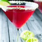 Cranberry and vodka in a clear martini glass with sugary green crust around the rim with text Cape Cod Cosmo with Sugar Lime Rim