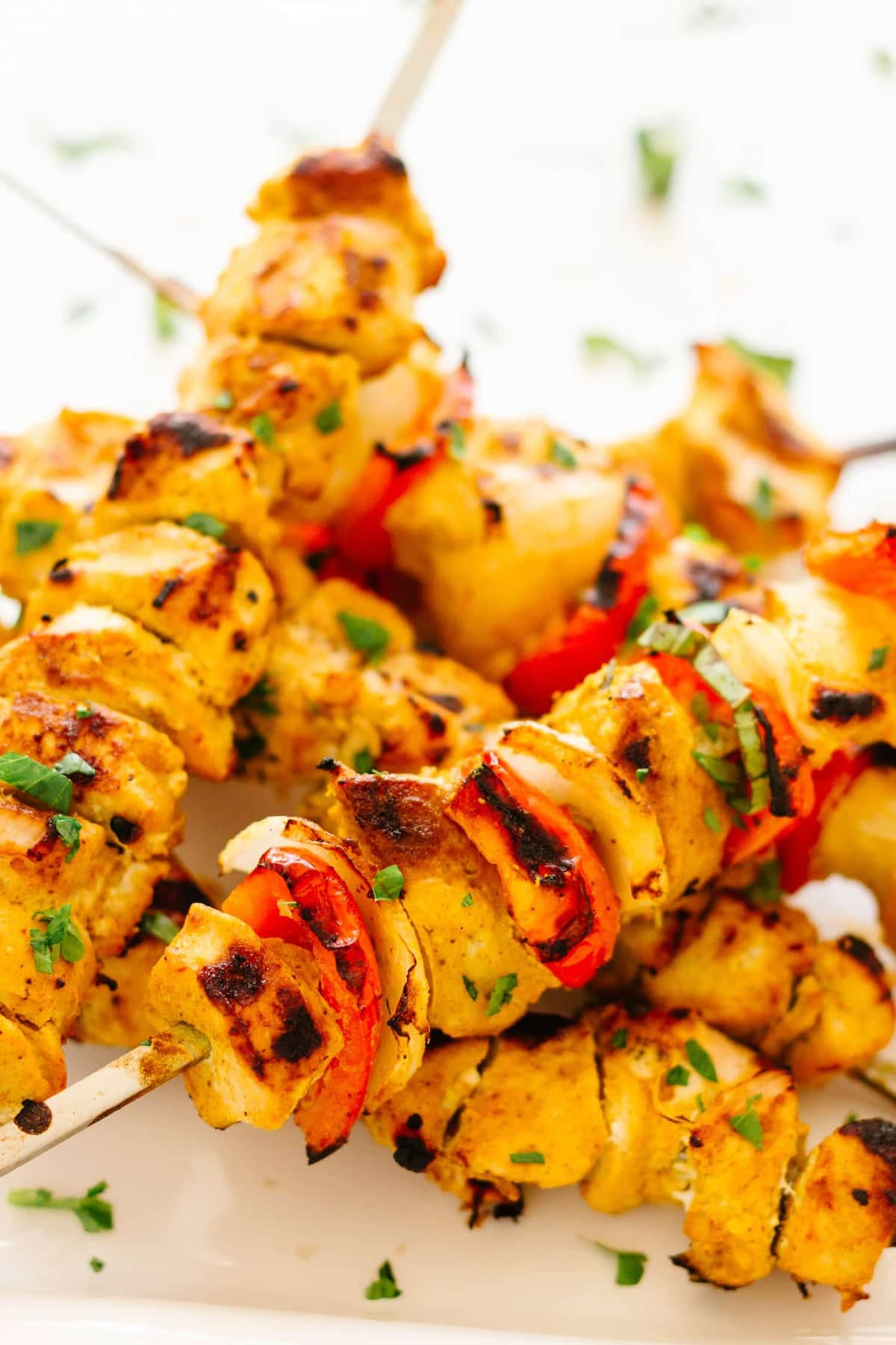 pieces of Tandoori chicken, onion, and red pepper on wooden skewers