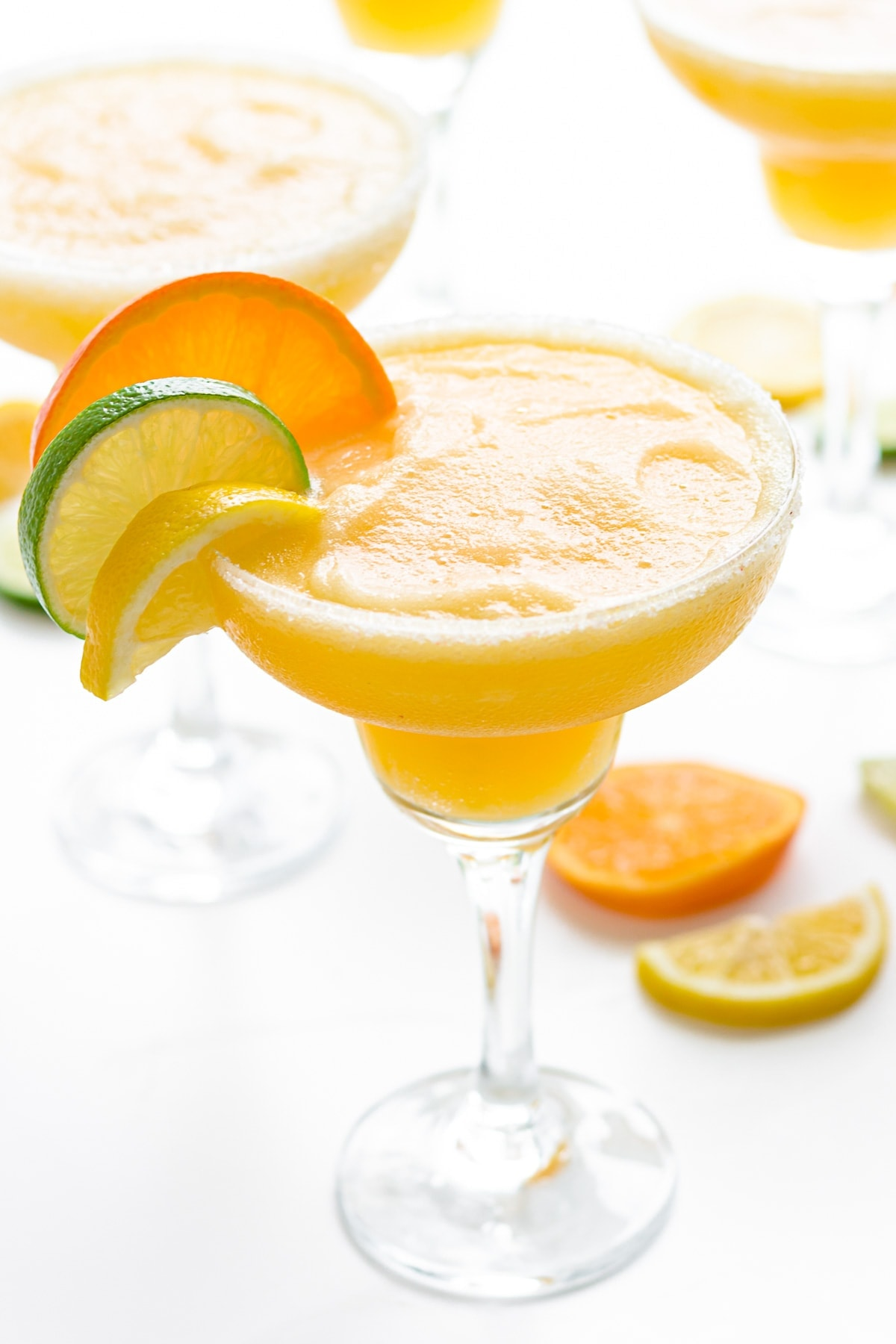 Bright orange frozen margarita in a glass with slices of lemon, lime, and orange on the rim.