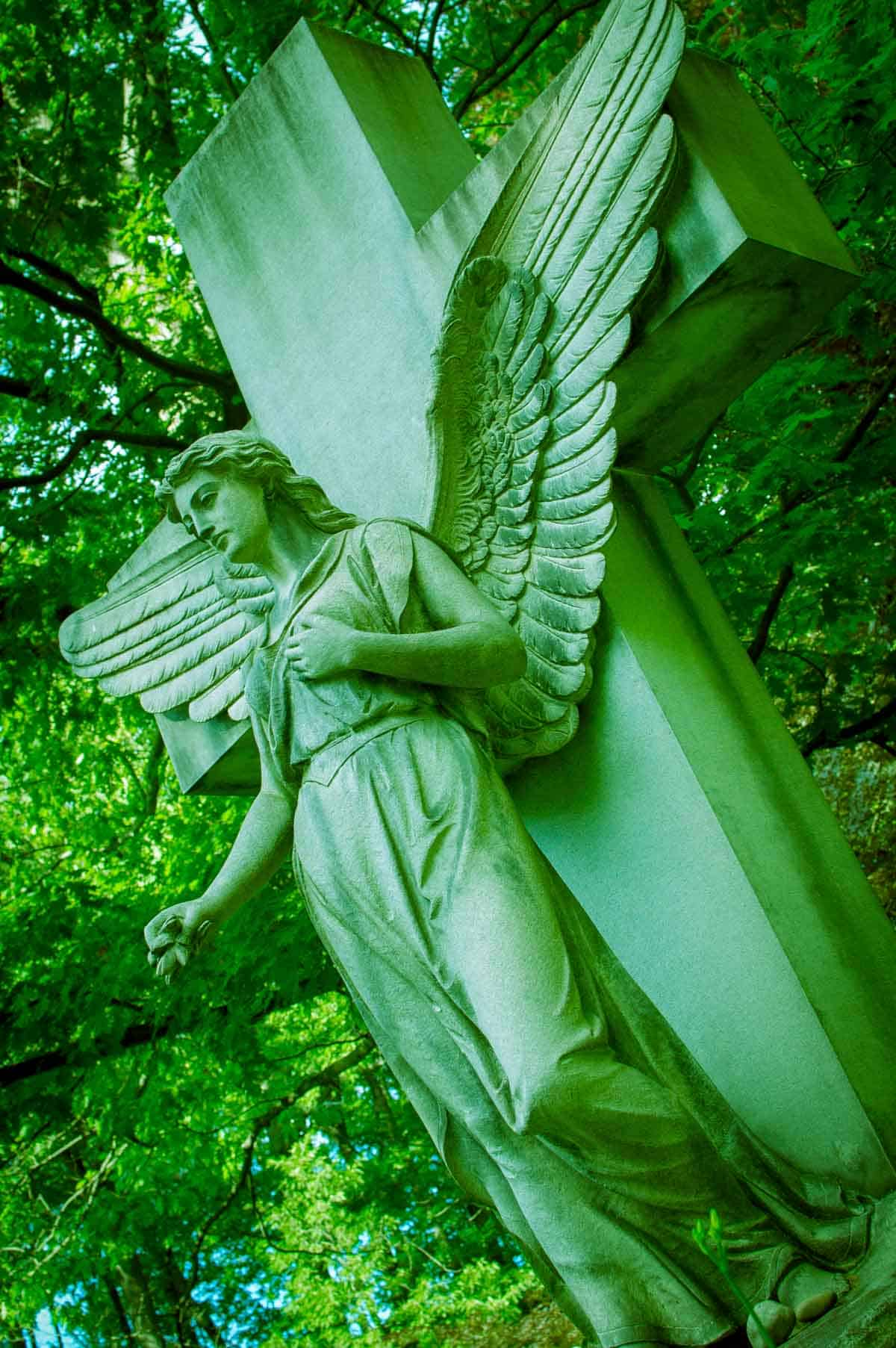 Cement cross and angel statue in a forest